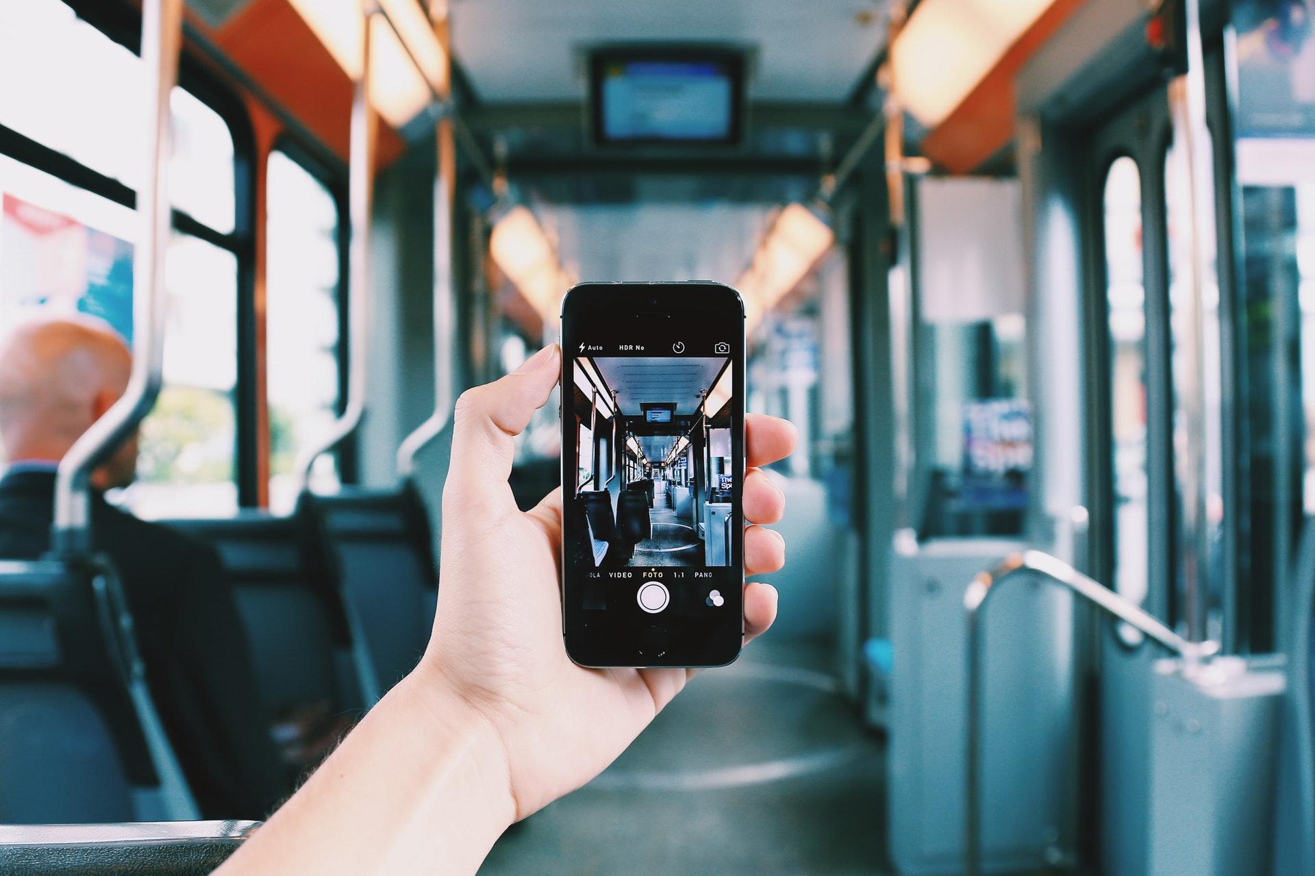 Hand hält Smartphone in einem leeren Linienbus hoch.