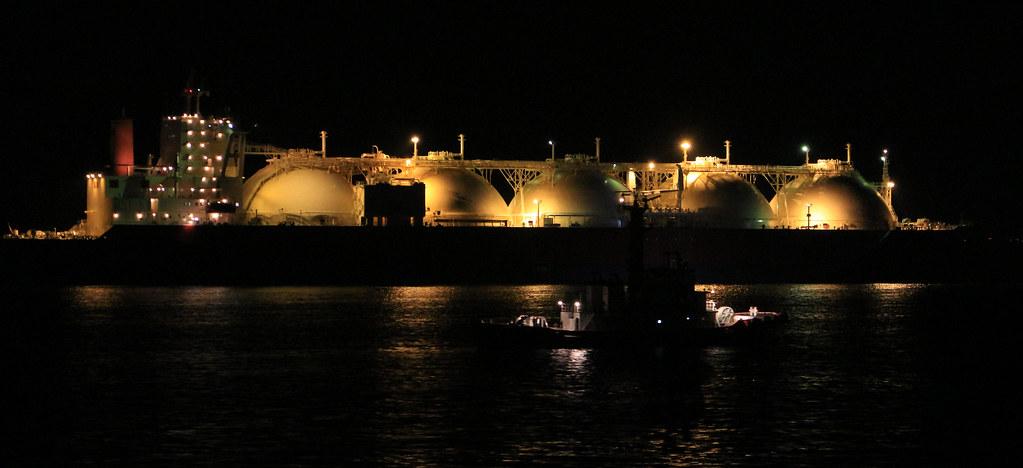 Ein beleuchteter LNG-Tanker bei nacht im Hfen