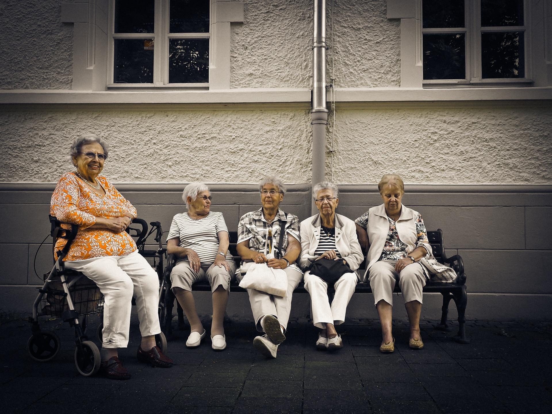 Gruppe von Seniorinnen auf einer Bank, eine mit Rollator.