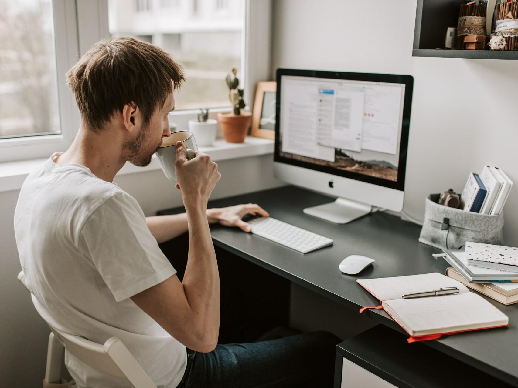 Junger Mann sitzt am Computer und nimmt einen Schluck aus der Kaffeetasse.