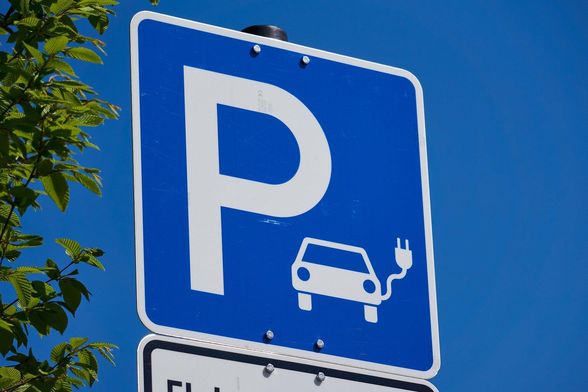 Verkehrsschild Parkplatz mit Ladesäule für Elektroautos, fotografiert im Freien.