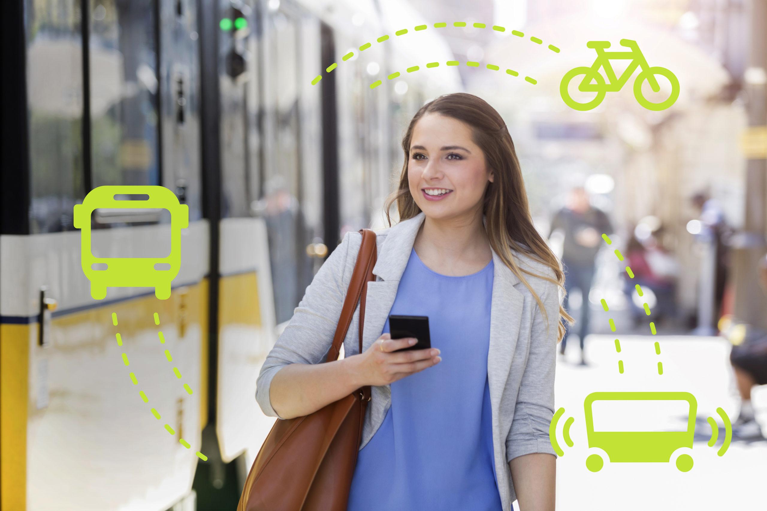 Junge Frau mit Handy in der Hand vor einer Bahn am Bahnhof