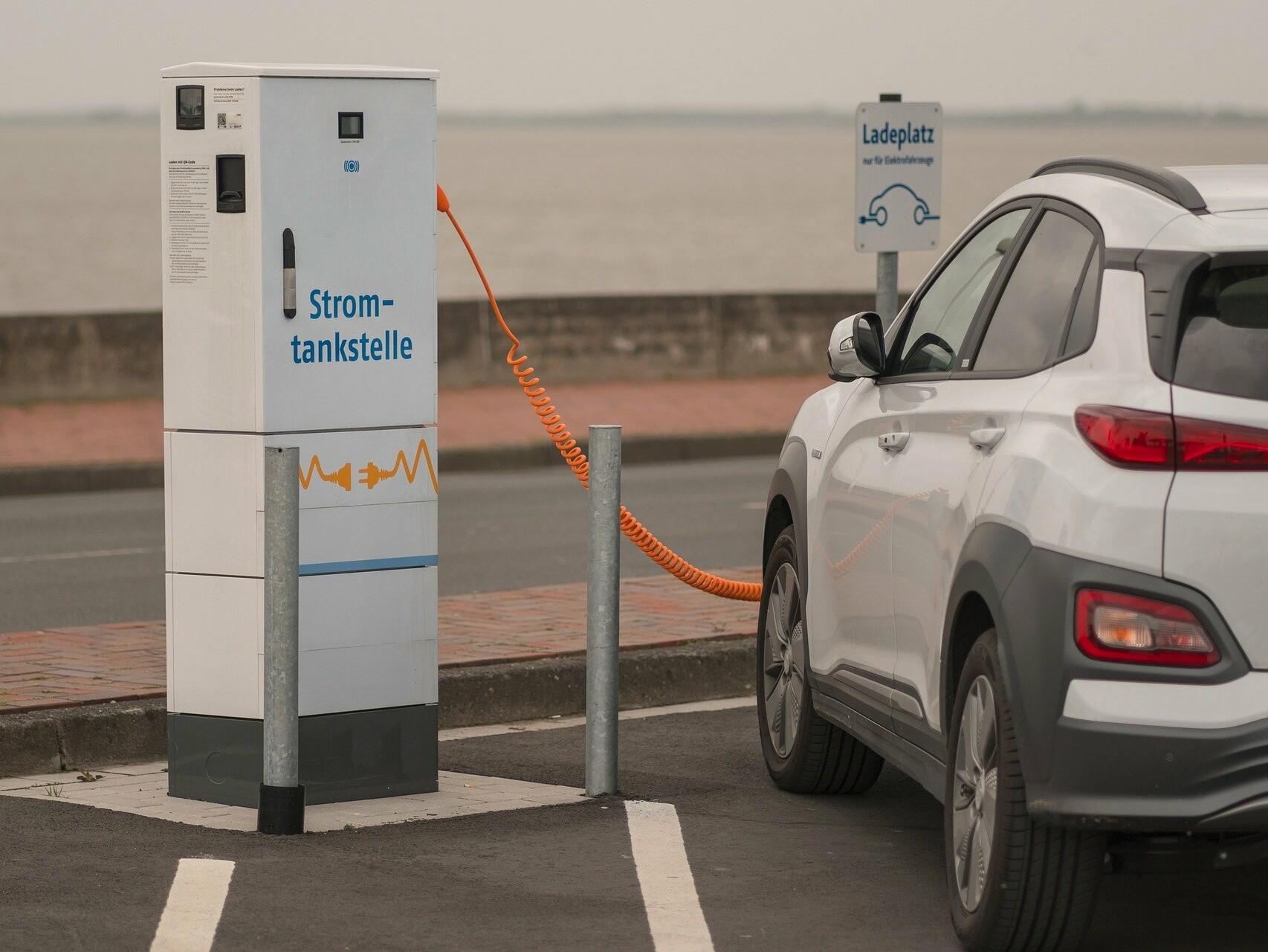Ein Elektroauto wird an einer Ladesäule auf einem Parkplatz geladen.