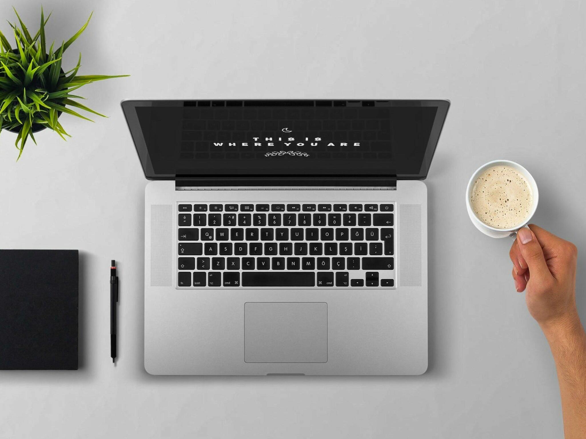Ein Arbeitsplatz mit Kaffe, Computer und Handy.