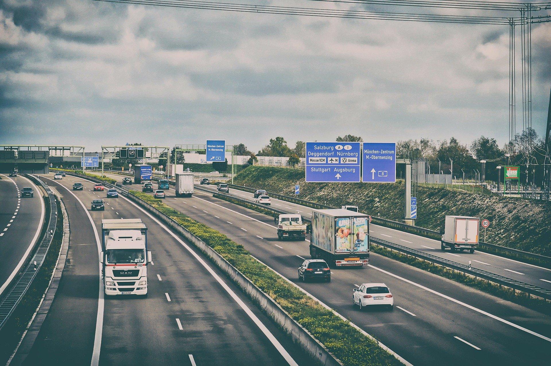 Blick auf eine mehrspurige Autobahn mit Lkws und Autos.