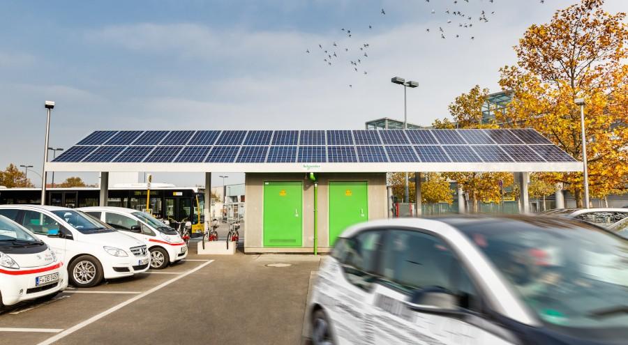 Großer Parkplatz mit E-Autos und Solarladeanlage
