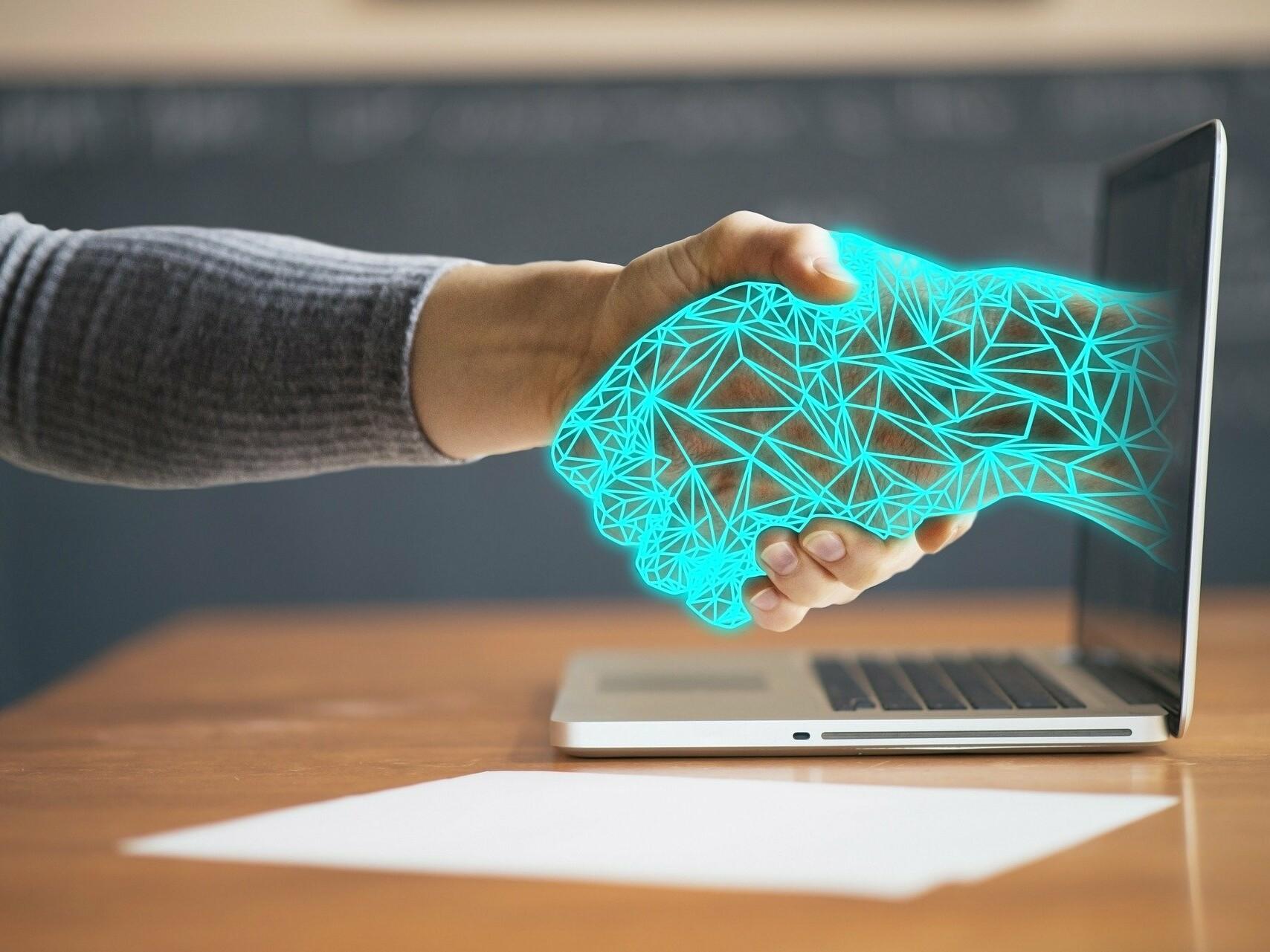 Handschlag zwischen menschlicher und animierter Hand, die aus einem Computerbildschirm kommt.