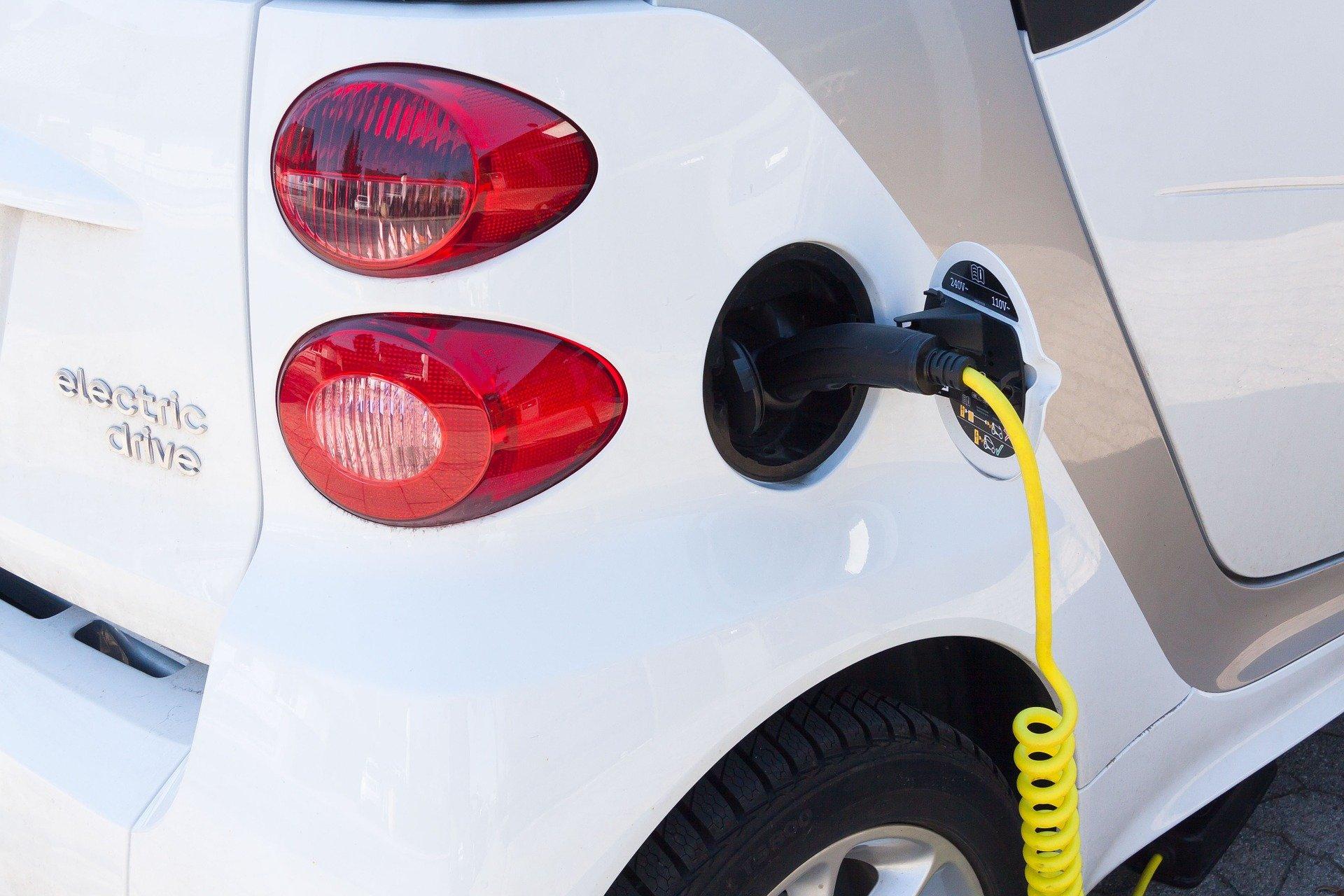 Über ein gelbes Ladekabel wird ein weißes Elektroauto geladen.