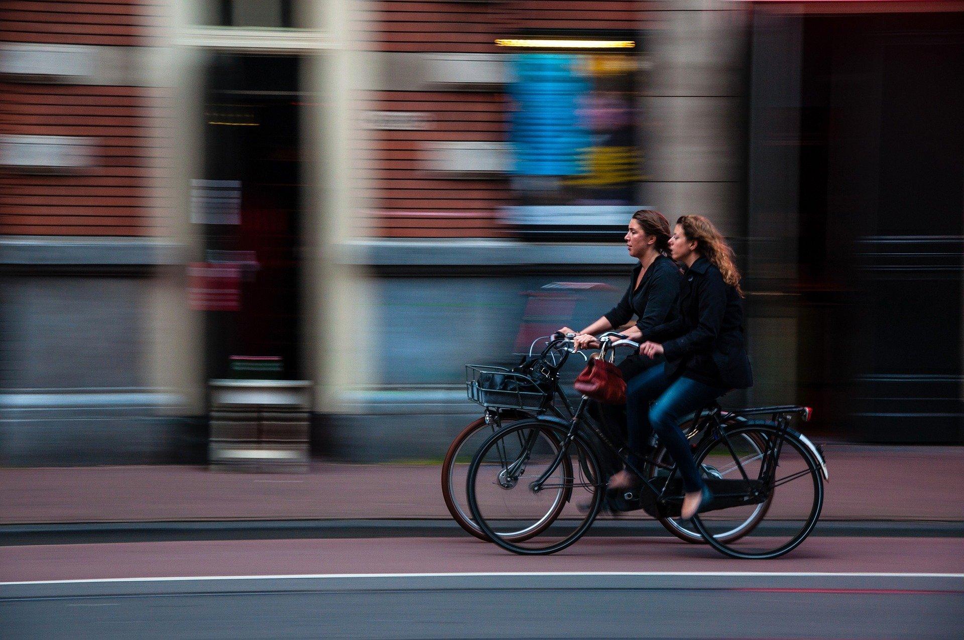 Zwei Frauen fahren nebeneinander auf einem Radweg in der Innenstadt.