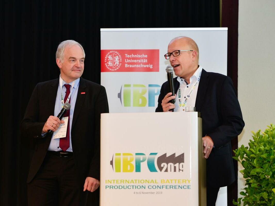 Zwei Herren stehen mit Mikro am Rednerpult bei der IBPC 2019 in Braunschweig.