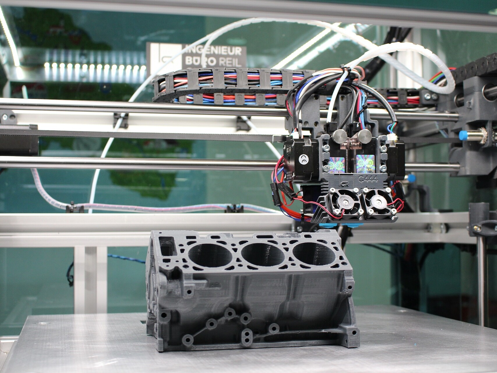 Ein 3D-Drucker druckt einen Motorblock aus Kunststoff.