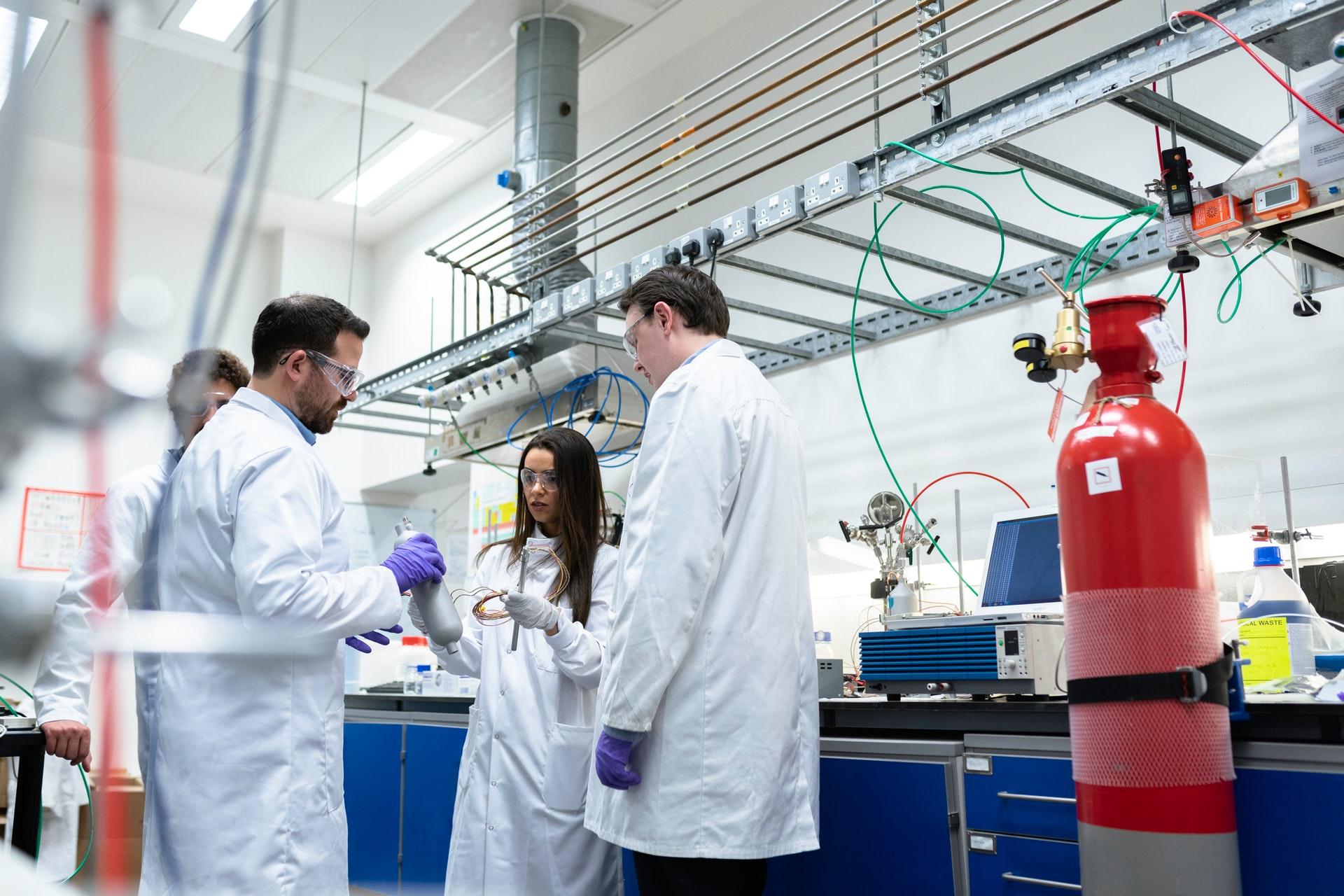 Eine Frau und drei Männer mit weißen Kitteln im Labor neben einer roten Gasflasche.