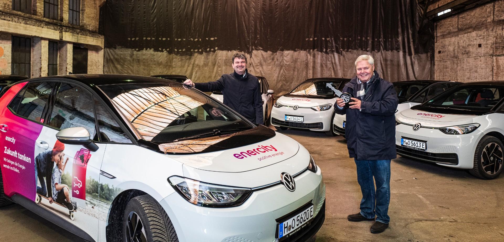 Zwei Herren stehen in einer alten Lagerhalle umringt von E-Autos von VW.