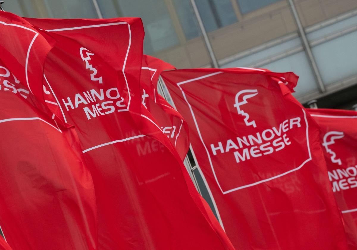 Rote Flaggen mit dem Logo der Hannover Messe vor einer Messehalle.