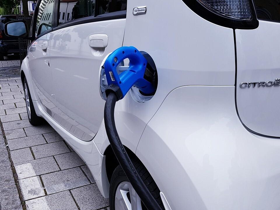Elektroauto wird auf einem Parkstreifen in der Innenstadt über ein Kabel aufgeladen.