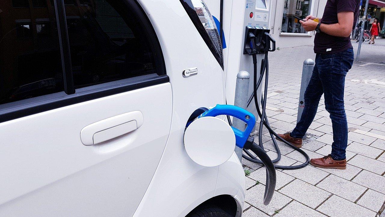Ein Elektroauto wird an einer Ladestation aufgeladen, daneben steht ein Mann mit braunen Schuhen.