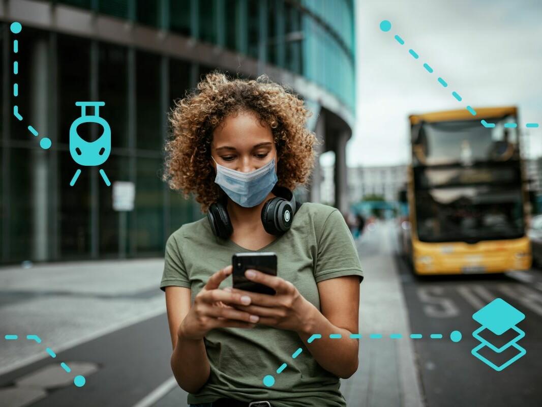 Eine junge Frau steht an einer Bushaltestelle und schaut auf ihr Smartphone.