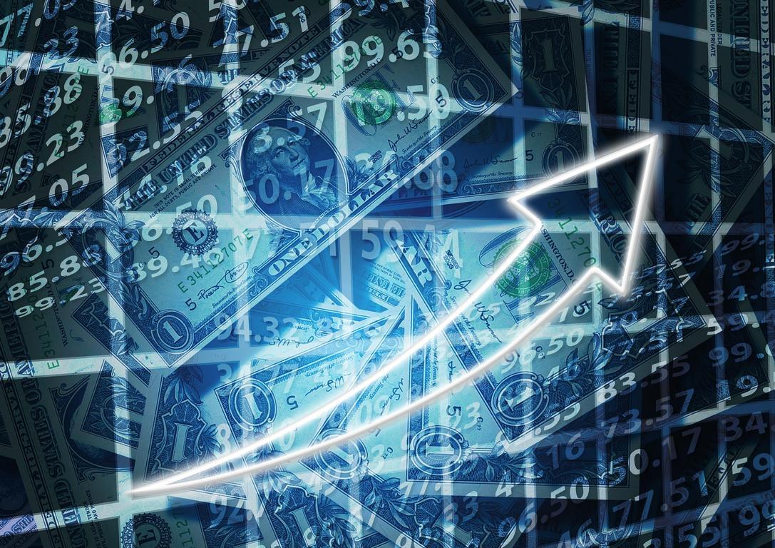 Aufsteigender Pfeil mit Dollar-Noten im Hintergrund.