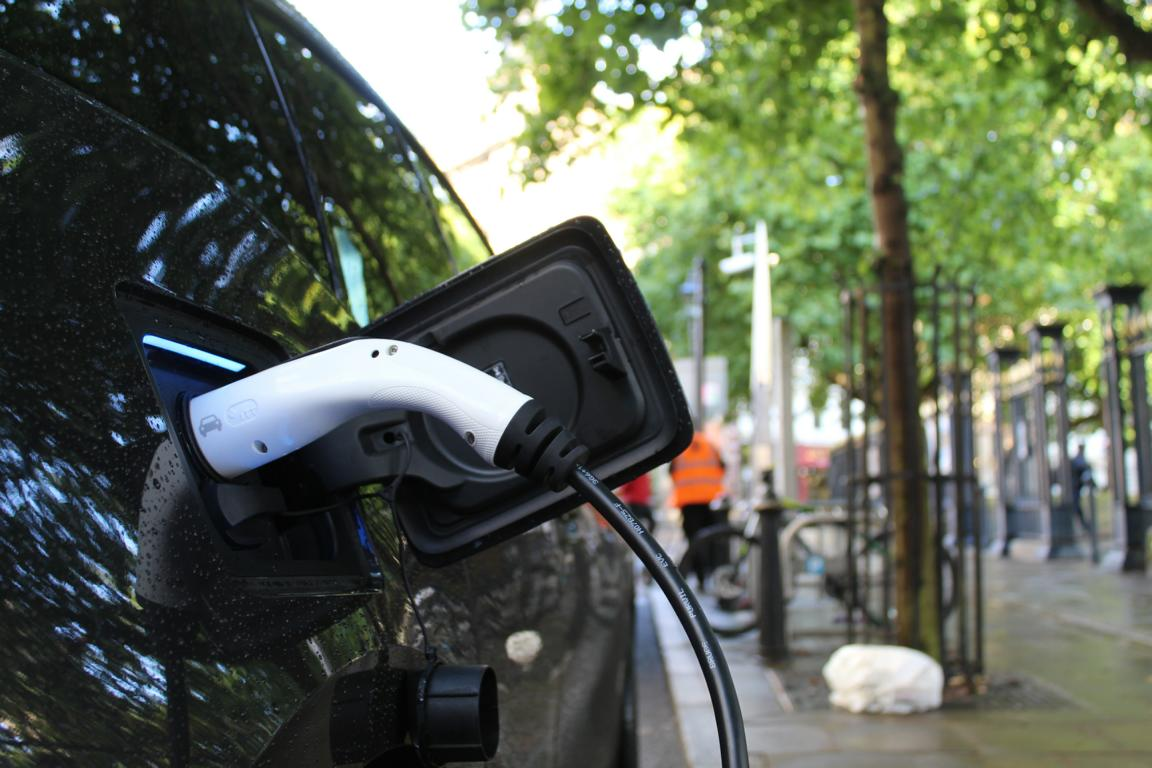 Nahaufnahme: Ein Auto wird elektrisch geladen.
