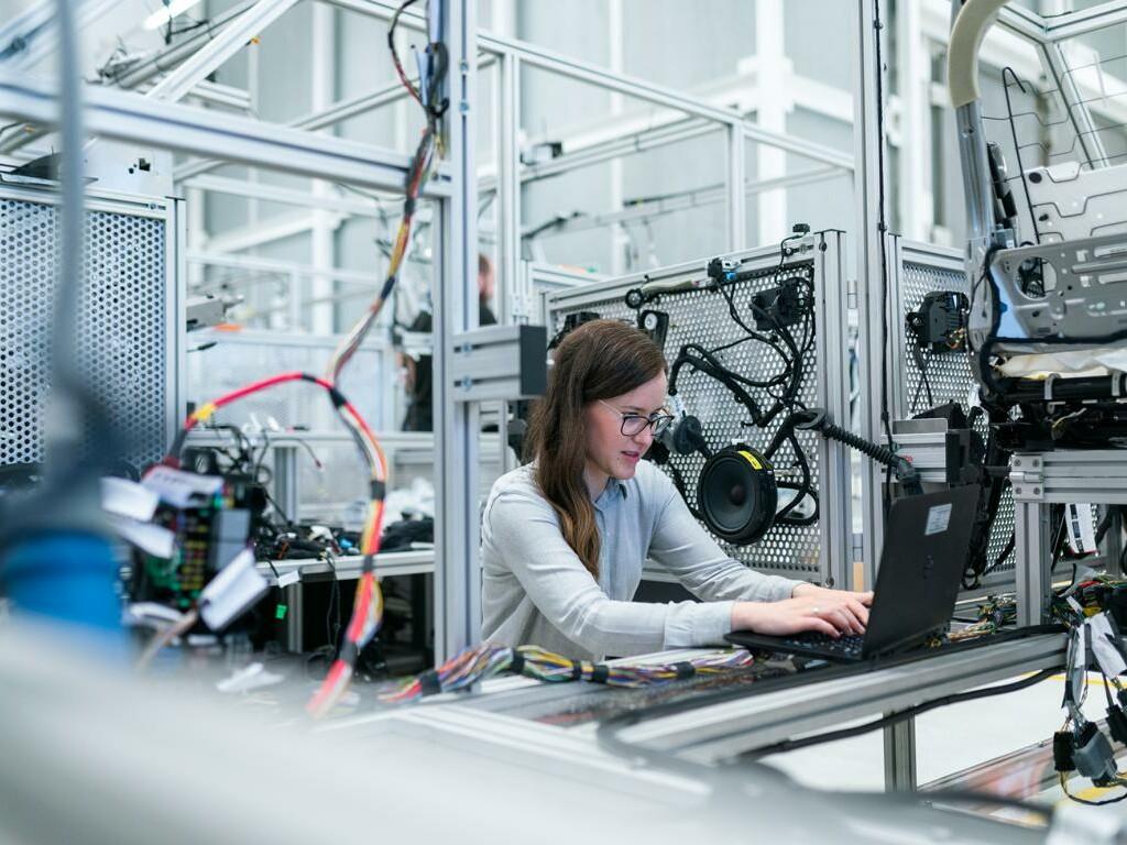 Frau arbeitet am Laptop, um sie herum ist viel Technologie.