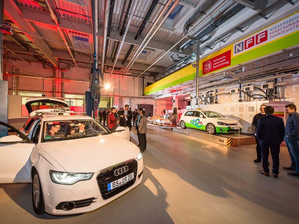 Ausstellungshalle der ACI.Mobility mit Pkws und Besuchern.